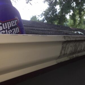 Roof gutter half cleaned with Super clean bottle