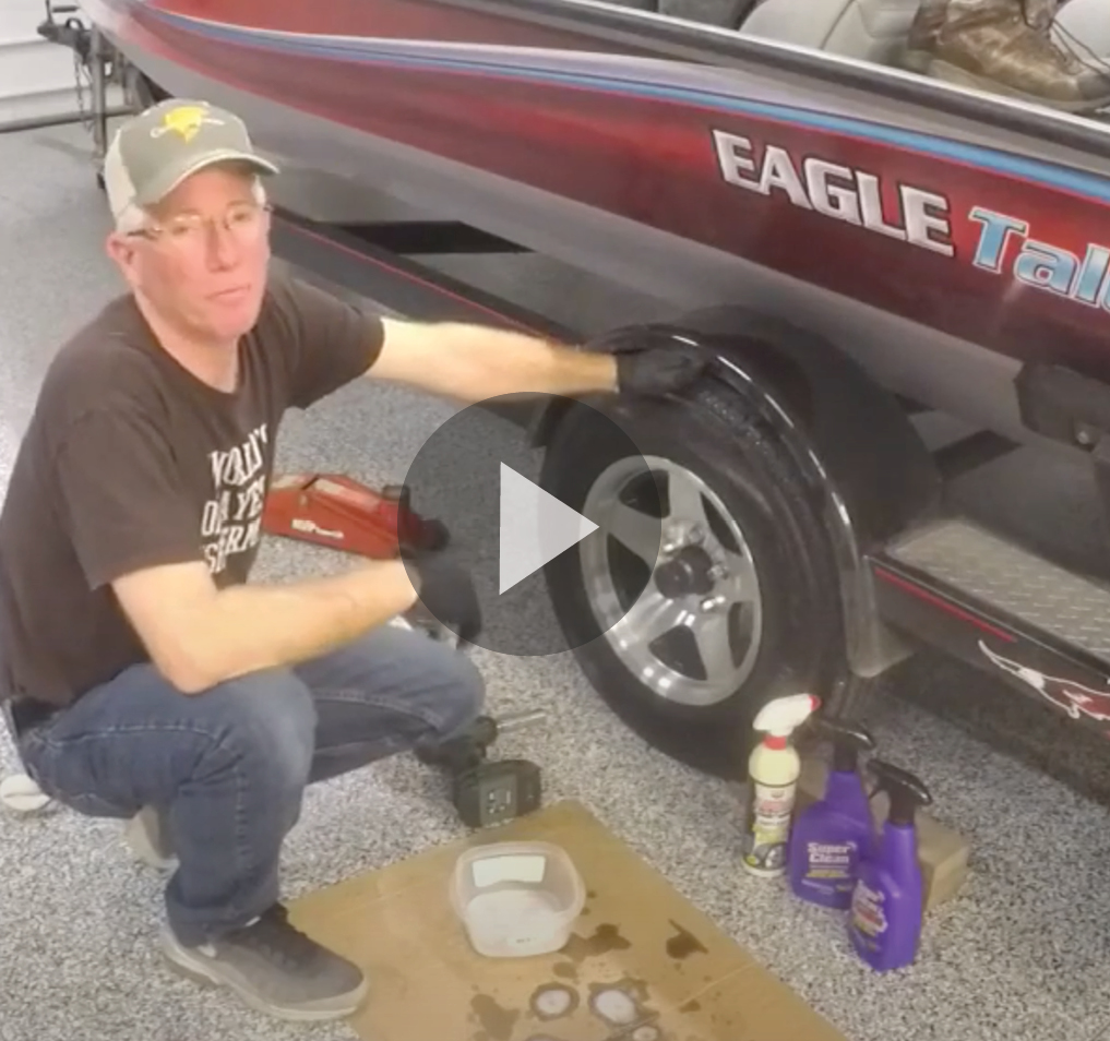 Still shot with play button of cleaning boat trailers video
